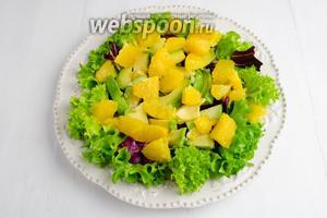 Сверху листьев разложить дольки авокадо и апельсина.