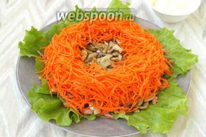 Далее в форме кольца выложить корейскую морковь (150 г).