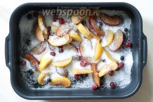 Сливы (200 г) и ягоды (50 г) помещаем в форму, посыпаем сахаром (50 г) и запекаем в разогретой до 180°С духовке 10 минут.