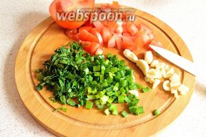 Пока готовится плов, нарежем оставшиеся продукты. 1/2 помидора режем кубиком, рубим зелень (15 г зелёного лука и 15 г петрушки). 2 зубчика чеснока я крупно порубила, а 3 оставила целиком.