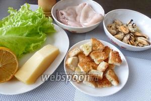 Для салата Цезарь с морепродуктами возьмём свежемороженые кальмары, подкопченные мидии, зелёный салат, сыр Пармезан, лимон, чёрный перец и сухарики из багета или булки. Как их готовить, я рассказывала в рецепте «салат Цезарь с рыбой».