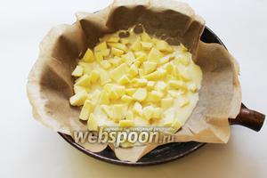 Форму для выпечки застелить вощёной бумагой, налить немного теста и уложить яблоки.