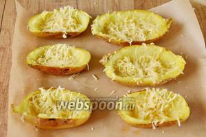 На мелкой тёрке натереть твёрдый сыр (50 г). Вытащите картофельные шкурки из духовки, уложите в каждую картофельную шкурку немного тёртого сыра, поставьте снова в духовку, чтобы сыр расплавился.