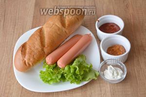 Для приготовления необходимы сосиски, 2 мини-багета, горчица баварская, майонез, кетчуп, лист салата.