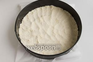 2/3 песочной крошки выложить в форму, застеленную пергаментной бумагой. Распределите равномерный слоем и утрамбуйте. Поставьте в холодное место.
