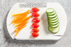 Тонко нарежем огурец (нам понадобится несколько тонких долек, 5 г) и паприку (10 г), 3 помидорки черри — на половинки или на четверти.