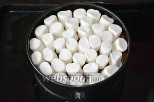 На готовый и ещё горячий торт выкладываем по периметру маршмеллоу (150 г).