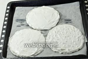 Противень выложить кулинарной бумагой и начертить 3 круга диаметром 20 см. Смазать слегка растительным маслом (1 ст. л.) и выложить белки в начерченные круги. Разровнять. 1 корж можно оставить с небольшими «пиками» сверху — это будет верхний корж в торте и он может иметь красивую бугристтую поверхность.
