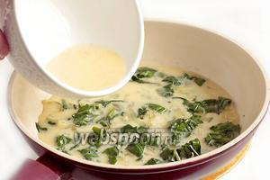 Как только шпинат размягчится, залить содержимое сковороды яичной смесью. Жарить на малом огне под крышкой.