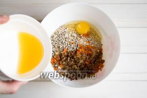 Смешать в посуде овсяные хлопья (120 г), яйцо (1 шт.), изюм и курагу. Засыпать семечки (30 г) и влить апельсиновый сок (35 мл). Тщательно перемешать смесь.