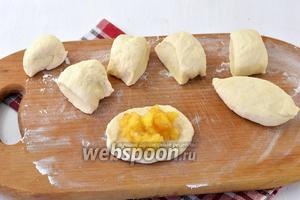 Разделить тесто на небольшие кусочки. Формировать из них лепёшки и на середину каждой выкладывать 1 столовую ложку начинки. Сформировать пирожки, хорошо защипнув швы.