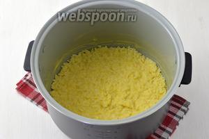 Чашу мультивраки (у меня мультиварка Полярис) смазать сливочным маслом. На дно выложить 1/2 часть риса и слегка утрамбовать.