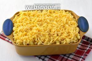 На сосиски выложить вторую часть макарон. Равномерно полить яичной смесью. Присыпать натёртым сыром.