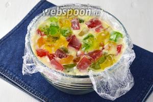 Глубокую куполообразную форму выложить пищевой плёнкой. Вылить в неё сметану и всыпать вперемешку нарезанные разноцветные кубики из желе. Накрыть сверху плёнкой и отправить в холодильникна 3-4 часа.