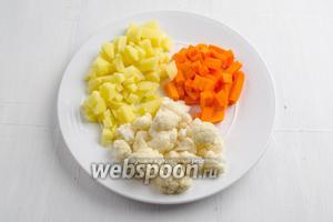 Тем временем картофель (3 шт.) и тыкву (100 г) очистить, вымыть. Нарезать кубиком. Цветную капусту (100 г) разделить на соцветия. Вымыть под проточной водой.