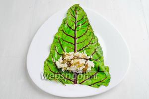 Разложить подготовленный лист на тарелке лицевой частью вниз. Срезать часть центральной прожилки на листе. Выложить начинку.