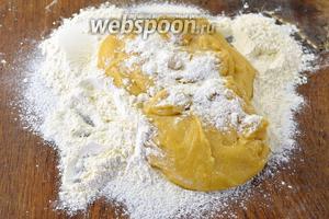 Переложить тесто на стол с 1 стаканом муки и начать замешивать тесто.