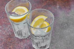 Слегка отжимаем лимонные дольки в бокал (можно слегка раздавить их пестиком, если очень твёрдые) и выкладываем их на кубики льда.