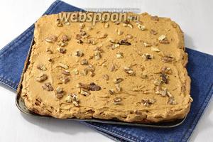 Выложить корж белками вверх. Смазать частью крема и посыпать частью орехов.