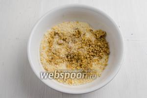 Панировочные сухари (4 ст.л.) смешать с оставшимися орешками (50 г).