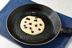 Разогреть на среднем огне сковороду. Слегка смазать её первый раз маслом. Выложить на середину сковороды 2 полных столовых ложки теста. Сверху разложить  несколько ягод черники. Выпекать до образования пузырьков на поверхности. Перевернуть на вторую сторону и дожарить панкейк до готовности.