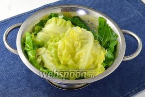 Капустные листья промыть и отварить в кипящей воде 2-3 минуты до мягкости. Срезать твёрдые прожилки.