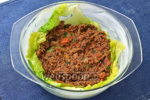 Форму для запекания смазать сливочным маслом. На дно формы выложить несколько капустных листьев и смазать их частью соуса. Сверху выложить часть начинки.