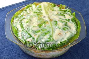 Повторять слои, пока не закончатся продукты. Последним слоем уложить капустные листья и смазать соусом.