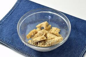 С хлеба (100 г) срезать корки, поломать и замочить на 5 минут в молоке (100 мл).