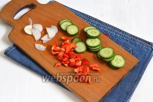 0,5 перца, 1 огурец и 1 помидор вымыть и высушить. 1 луковицу очистить. Огурец порезать кружочками, лук — тонкими полукольцами, а перец — кубиками.