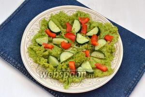 На салат выложить перец и огурцы. Приправить овощи солью.