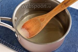 Соединить в кастрюле воду (80 мл), 50 г сахара и довести до кипения. Уменьшить огонь и готовить, пока сироп не уварится вдвое. На это уйдёт приблизительно 10 минут.
