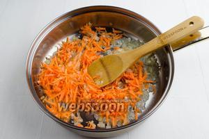 Морковь (1 шт.) очистить. Измельчить крупно на тёрке. Добавить подготовленную морковь к луку. Продолжить жарить до мягкости моркови.