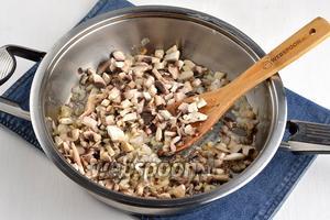 Добавить очищенные и порезанные шампиньоны (300 г) и готовить ещё 8 минут. Приправить по вкусу солью и перцем.