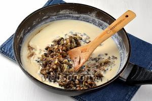 Влить в мучную смесь сливки (200 мл), выложить луково-грибную смесь, довести до кипения и томить 5 минут.