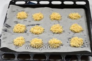 Выложить сыр на противень с пергаментной бумагой (иногда выкладывают даже на противень без бумаги) небольшими кучками. Оставляйте между кучками достаточно места, так как сыр будет растекаться. Подровняйте края кучек ножом.