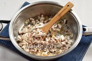 Добавить очищенные и мелко порезанные шампиньоны (300 г). Готовить ещё 6-7 минут.