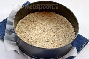 Форму выложить кулинарной бумагой и смазать подсолнечным маслом (0,5 ст. л.). Утрамбовать смесь в форму, в которой будет выпекаться и бисквит. Отправить в холодильник на 1 час.