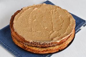 Каждый корж смазать тонким слоем крема. Также смазать кремом верхний корж и бока.