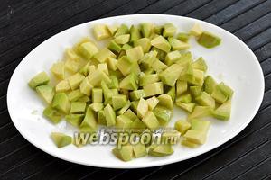 Авокадо (1 шт.) очистить от кожуры, порезать кубиками, обильно сбрызнуть лимонным соком (2 ст. л.) и перемешать.