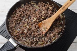Добавить 400 г фарша, приправить солью (0,75 ч. л.) и перцем (0,3 ч. л.) и готовить, помешивая, 20 минут. Охладить. В охлаждённую начинку добавить 2 зубчика чеснока, пропущенного через чесночницу, и перемешать.