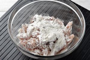 Посыпать филе мукой (2 ст. л.) и хорошо перемешать, чтобы брусочки мяса со всех сторон покрылись тонким слоем муки.