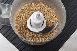 Переложить орехи в чашу кухонного комбайна и измельчить до крошки (насадка «металлический нож»).
