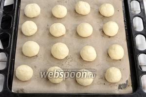 Из теста сформировать небольшие шарики и выложить их на противень с пекарской бумагой.
