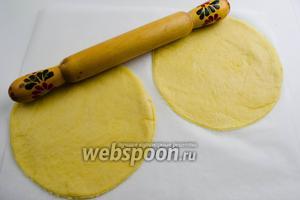 Раскатать в 2 круга, приблизительно 15-17 см в диаметре, сразу на пергаменте. Выложить пергамент с заготовкой в противень.