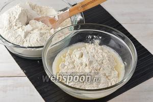 Муку просеять и постепенно добавлять её в миску, замешивая круговыми движениями, ложкой, тесто.