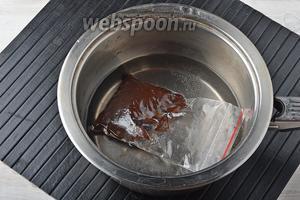 Шоколад (50 г) мелко порезать и поместить в пакет, который герметично закрывается. В кастрюле довести 200 мл воды до кипения. Снять кастрюлю с огня, а в горячую воду поместить пакет с шоколадом на 20 секунд. Вынуть пакет и руками размять шоколад внутри. Если вы почувствуете, что там остались небольшие твёрдые кусочки шоколада, опустите пакет с шоколадом в горячую воду ещё на 3-5 секунд и опять разомните.