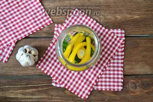 Сладкий перец (2 штуки) помыть, очистить от плодоножки и семян, нарезать соломкой. Очистить чеснок (6 зубков). Разложить овощи по баночкам.