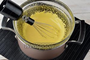 В кастрюле нагреть воду до 80°С и уменьшить огонь до минимума. На кастрюлю с водой сверху выложить миску с желтками. Вода в кастрюле не должна касаться дна миски. Взбивать желтки миксером 4-5 минут, пока они не станут пышными.