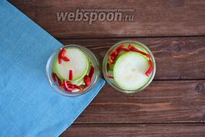 Острый перец помыть (2 штуки), очистить от плодоножки и семян, нарезать соломкой. Чеснок (2 головки) очистить. Разложить овощи по баночкам.
